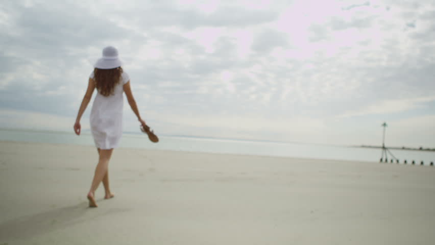 Girl in a white dress walking on the beach images