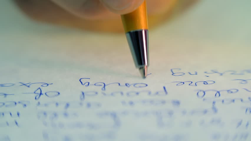 Pen writes a letter on paper. Closeup. Dolly shot. Shallow depth of field #10014608