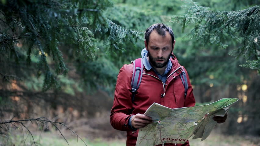Young, lost man with a map looking for direction in forest