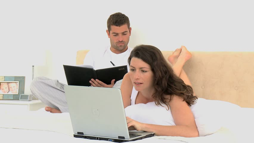 Couple laughing after watching a video on the laptop lying on the bed at home