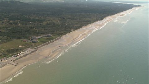 AERIAL France-Opal Coast 2006: Beach to the south of Hardelot-Plage, waves breaking, long sandy stretch, diagonal pan