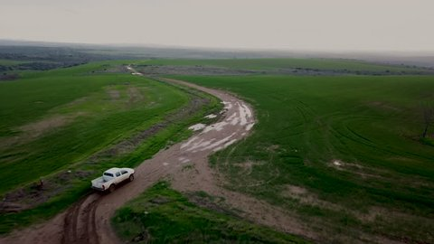 Aerial view of a pick-up truck driving thrugh a muddy field in winter