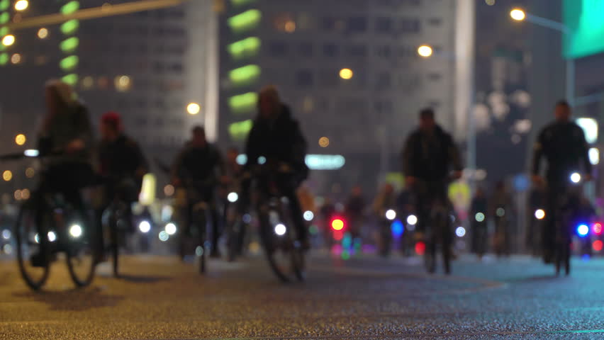Lot of cyclists ride during night cycling bike, bicycle parade in blur by illuminated night city street. Crowd of people on bike. Bike traffic. Concept sport healthy lifestyle. Bright shining lights