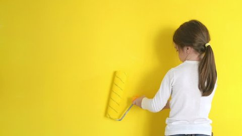 funny little girl gingerly paints the walls with a roller in the room
