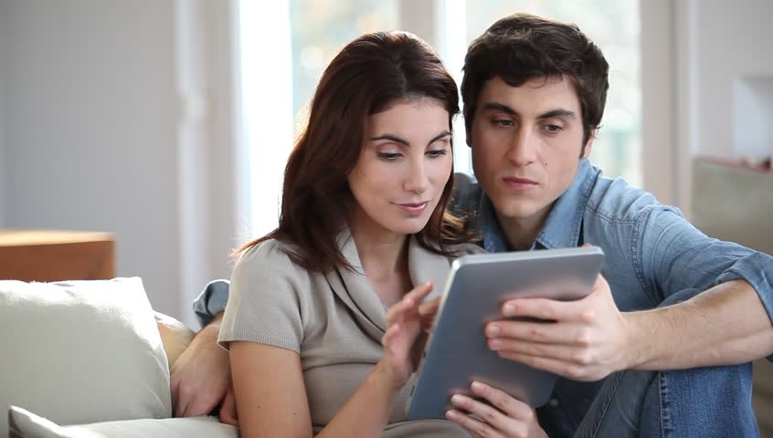 Couple sitting on sofa with touchpad