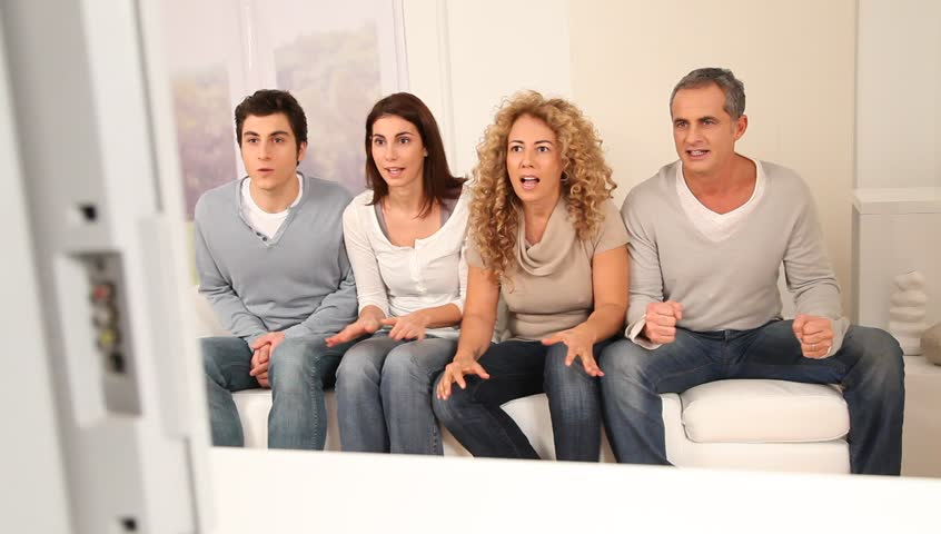 Group of friends watching football game on tv