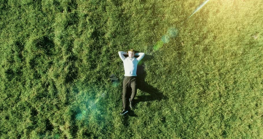 Aerial UHD 4K view. Vertical motion flight over businessman lying on fresh green meadow at sunny summer morning. Top view on handsome relaxing man. | Shutterstock HD Video #1006576948