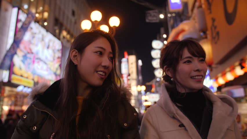 Two friends walking through bright Japanese streets dotombori
