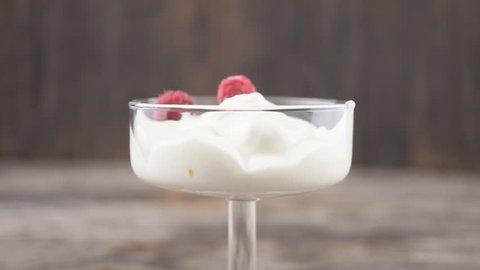 Raspberry falls in a glass of yogurt. Milk shake.