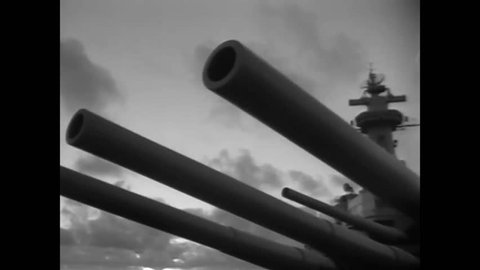 CIRCA 1950 - The UN flag is hoisted on the USS Missouri, while sailors load projectiles into the breach.