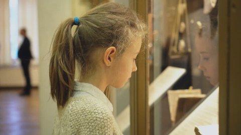 Little girl exploring expositions in museum.