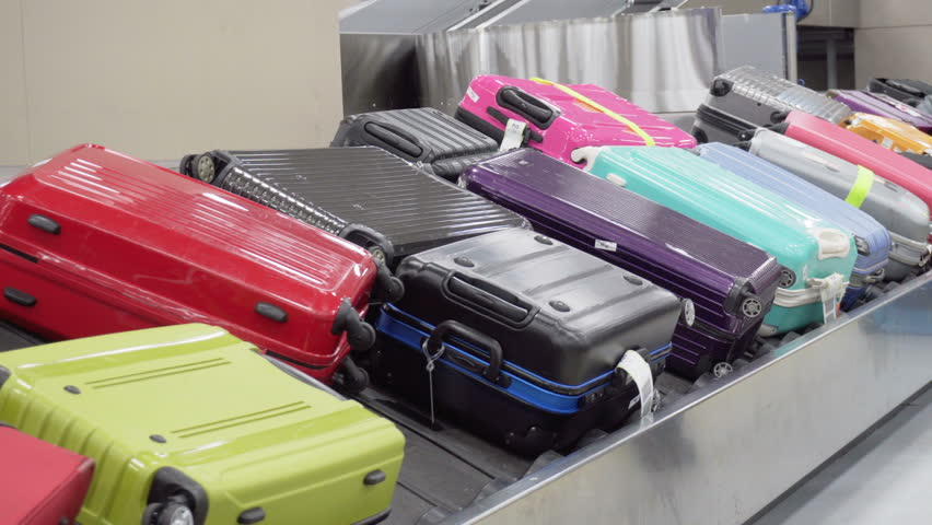 Suitcases on moving luggage conveyor belt at arrival area of passenger terminal. Colorful bags on baggage carousel. | Shutterstock HD Video #1006620628