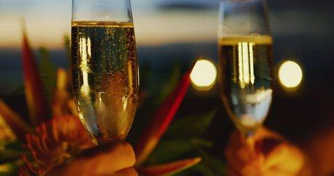 Couple celebrating drinking champagne at sunset