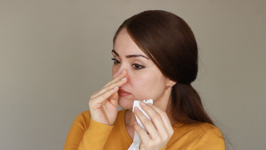 Portrait of a young woman who sneezes and holds a handkerchief in his hands. Allergic reaction of the nose. Sneezing