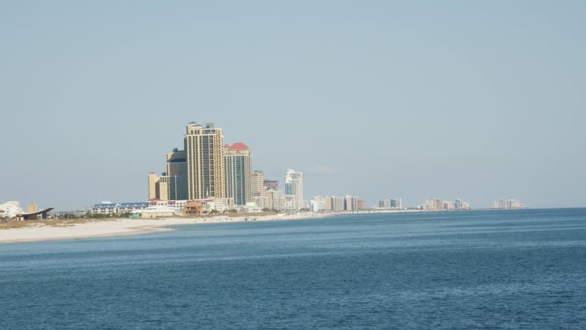 Slight panning shot of a seaside resort with high-rise apartments or hotel accommodation across a calm blue ocean on a sunny day