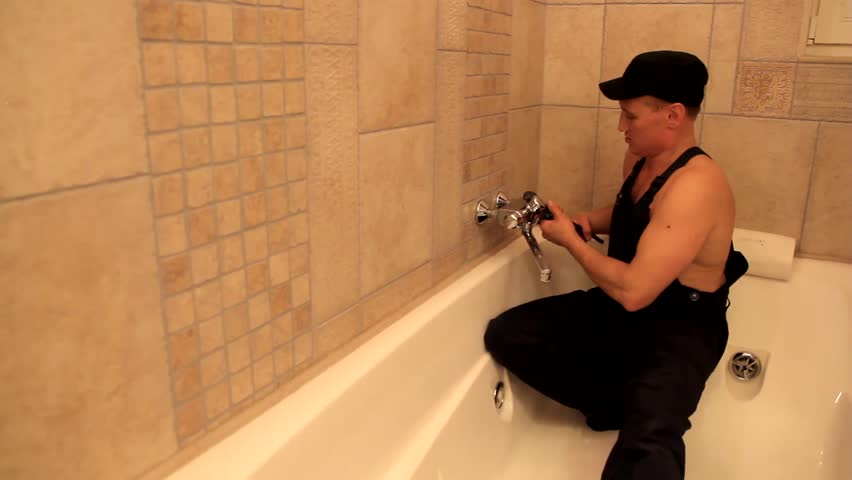 Plumber repairing faucet inside bath and sexy nurse near him.   Adult film parody.  Funny movie