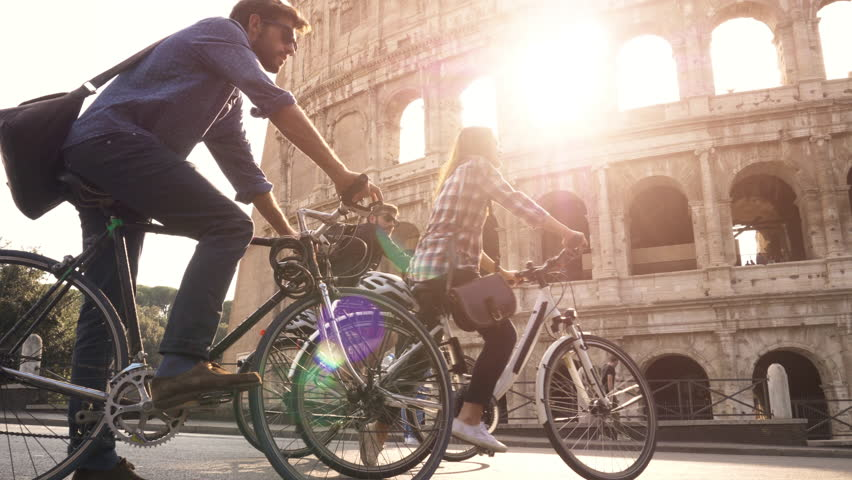 Three happy young friends tourists riding bikes with backpacks at Colosseum in Rome on sunny day slow motion camera steadycam | Shutterstock HD Video #1006665208