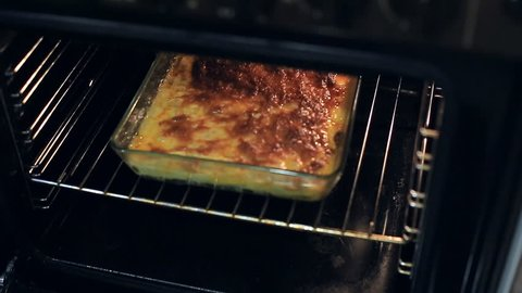 The housewife takes out the lasagna from the oven. homemade food
