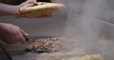 Piling chopped steak and onions into a long roll, creating a Philly cheesesteak, in slow motion