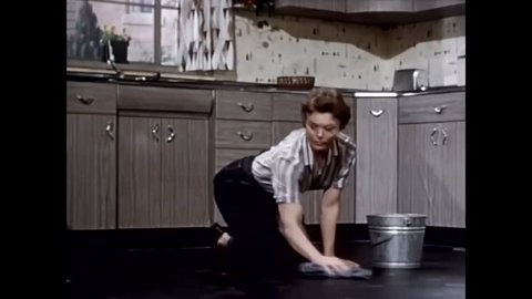 CIRCA 1959 - A housewife laboriously cleans the floor with a rag and soapy water.
