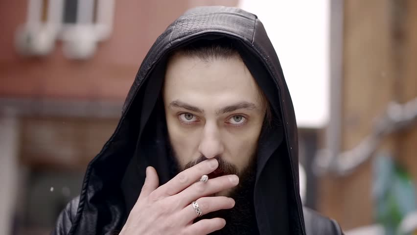 Close-up portrait of mysterious man with a beard in a leather cloak with a hood he is going day and smokes a cigarette