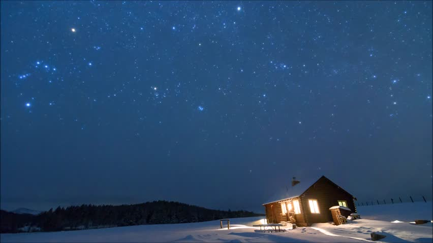The stars move above a rustic log cabin on a frigid winter night in the Bighorn Mountains. Clouds slowly obscure the sky.
