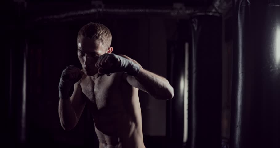 Kickboxer shadow boxing as exercise for the fight. Fighter training punching. Boxing in the darknes. Young boxer training in the gym