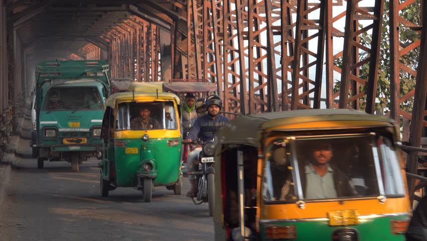 NEW DELHI, INDIA - DEC 24: Motorcycles, auto rickshaws and cars crossing bridge on December 24, 2017 in New Delhi, India
