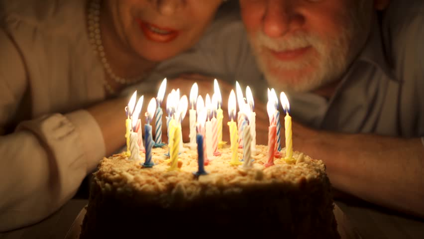 Loving senior couple celebrating anniversary with cake at home in the evening. Happy elderly family hugging, cuddling together, make wishes and blowing out candles. Focus on the cake.