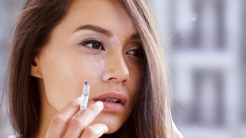 Close up view of brunette woman smoking cigarette at home