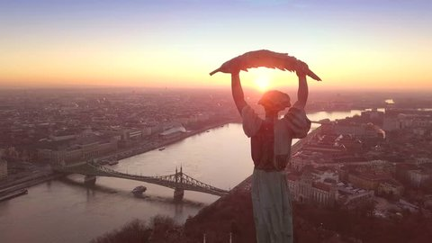 Budapest, Hungary - 4K aerial footage at sunrise of drone flying around of Statue of Liberty with the skyline of Budapest at background
