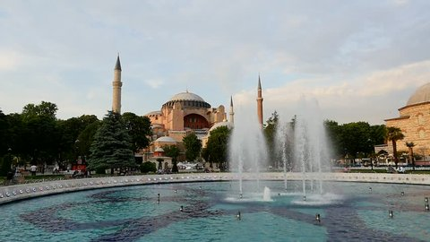 Slow motion birds fly over Hagia Sophia (Aya Sofya) museum and fountain view from the Sultan Ahmet Park in Istanbul, Turkey
