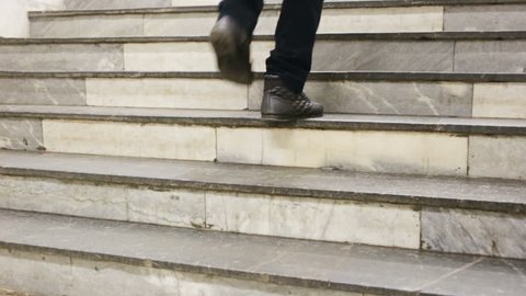 The man climb up the stairs. The guy dressed in slacks and winter boots. Medium shot, real time, amid flights of stairs, marble stairs.