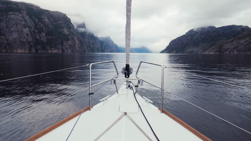 Nose part of ship on waves. Move forward on sea in great white sailing yacht. Fine ripples along quiet surface of water. Beautiful Nordic landscape. Blue sea, gray rainy sky and high mountains in fog | Shutterstock HD Video #1006813708