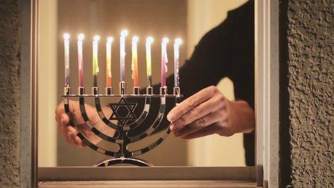 Hanukkah menorah candles displayed by window at night, Jewish holiday tradition