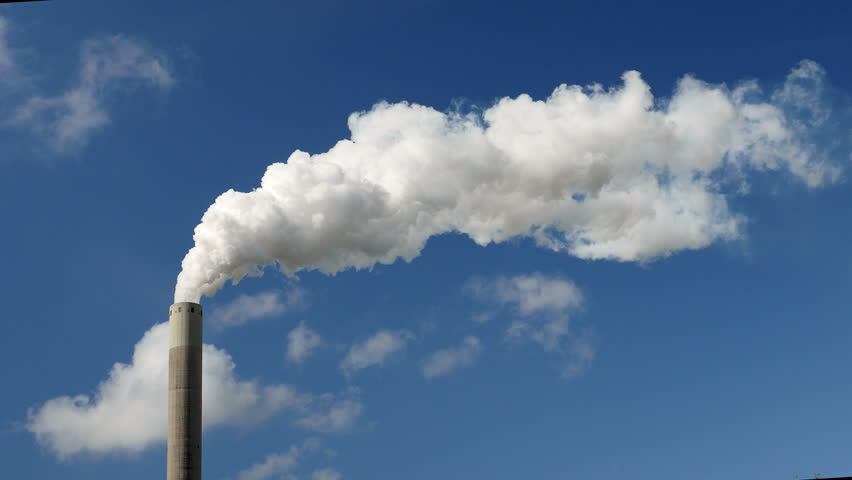 Medium shot of a smoke stack with a thick smoke plume. Beautiful blue sky and small patches of cloud.