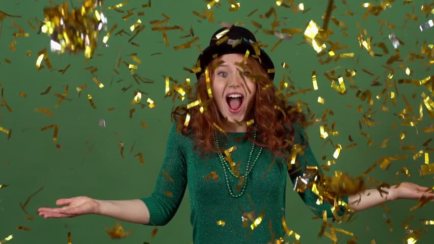 Young woman celebrating saint patrick's day on green wall moving in confetti | Shutterstock HD Video #1006849678
