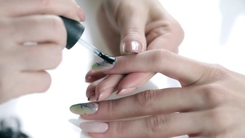 Women paints nails.Manicure Nail Art close up. Beautiful Nail Art Manicure. Nail designs with decoration.Manicure nail paint.