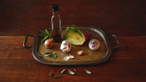 Cinemagraph – still life with garlic, onion, salad, oil, turnip and aromatic leaves