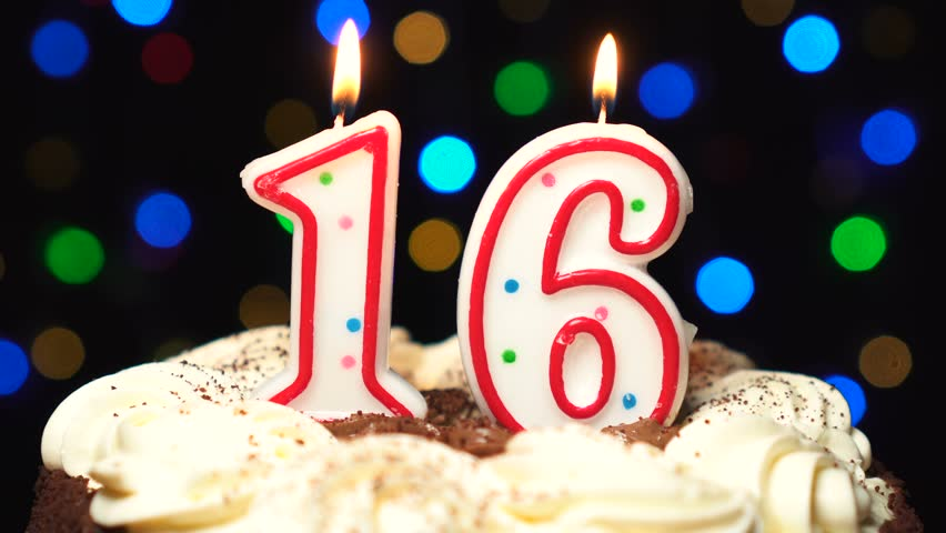 Number 16 on top of cake - sixteen birthday candle burning - blow out at the end. Color blurred background.