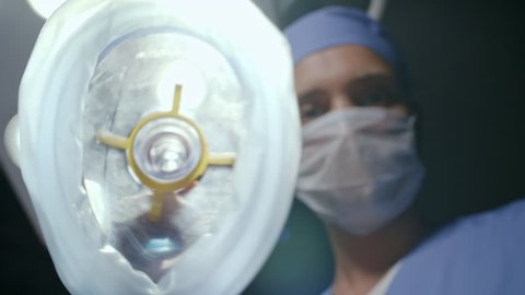 POV from eyes of patient of male anesthesiologist in scrubs putting anesthetic mask on camera