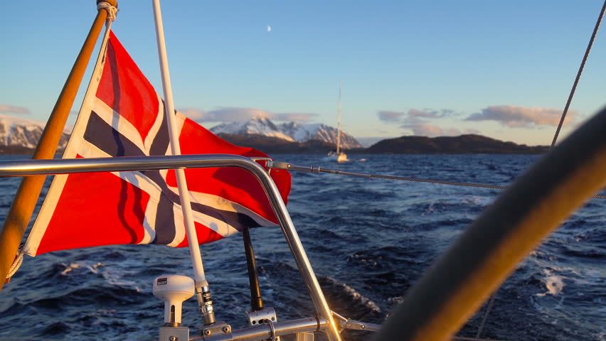 Norwegian flag on a yacht, Red with blue cross Norwegian national flag is slowly waving in the blue clear sky, Norwegian flag on the stern of a boat