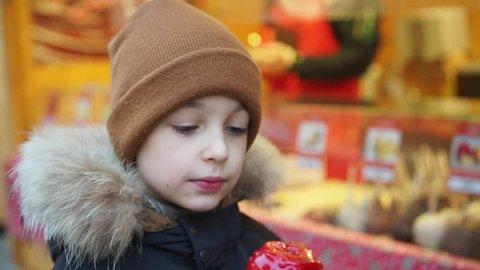 Boy bites a caramel Apple at the Christmas market