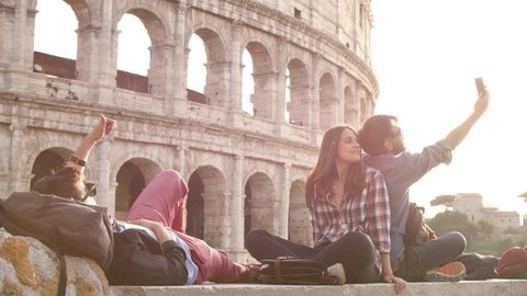 Three young friends tourists sitting in front of colosseum in rome at sunset taking selfies with smartphone with backpacks sunglasses happy beautiful girl long hair