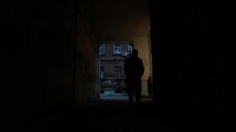 4k Alone man in coat goes through the dark noir arch in cold city