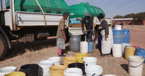 Water hardship. African people collecting water in containers from a remote water tanker due to severe drought in South Africa