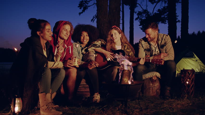 DOSPAT, BULGARIA - CIRCA 2017 - Group of happy friends play guitar around burn bonfire in the woods clap drink laugh and joke close friendship tourism travel party concept slow motion shot on red epic #1006991518