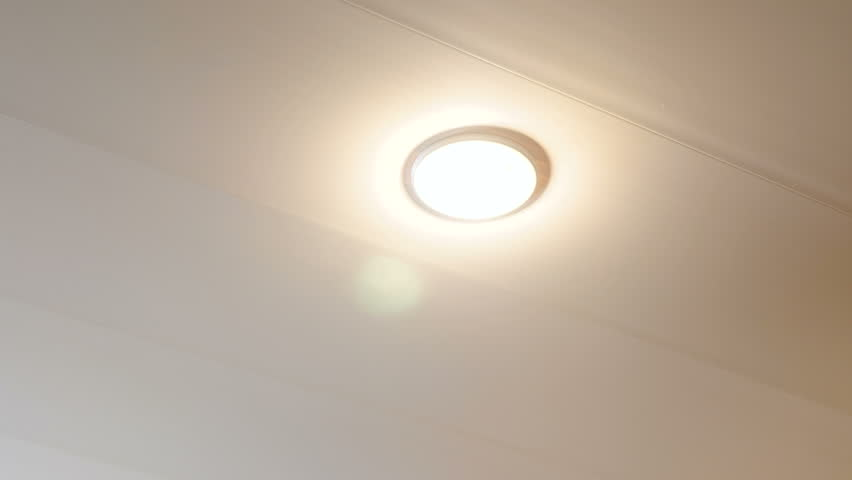 The man turns off the electricity and unscrews the light bulb from the ceiling.
