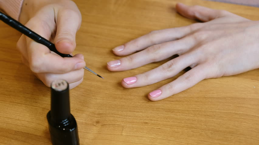 Homemade manicure painting nails in coral color self made woman doing yourself a manicure at home on the table close up 4k 4k solutioingenieria Image collections