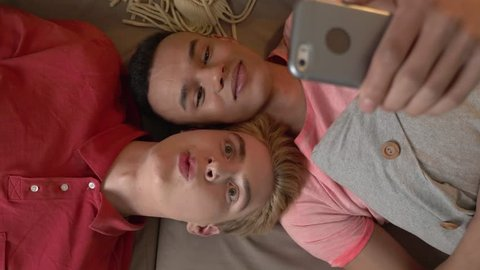 Happy international gay couple is lying on the couch and making selfies on a smartphone. Homeliness, LGBT lovers, happy gay family concept, laughing. Say hallo. Video chat. Top shoot 60 fps